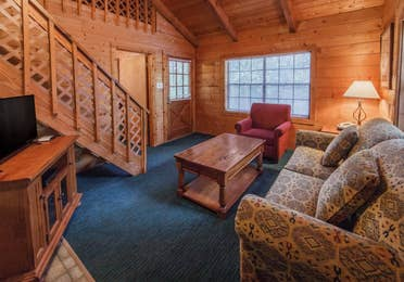 Living room in a one-bedroom log cabin at Holly Lake Resort in Holly Lake Ranch, Texas.