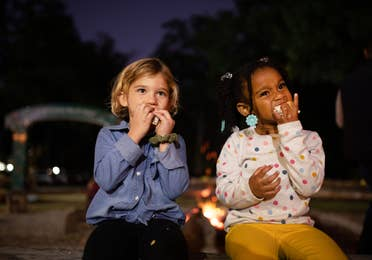 Two children eating s'mores outside during movie night at Falladays at Villages Resort.