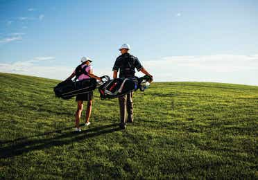 A couple carrying golf bags on their shoulders up a hill