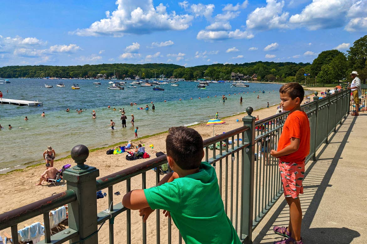 Two boys stand behind a rail overlooking the Beach of Lake Geneva.