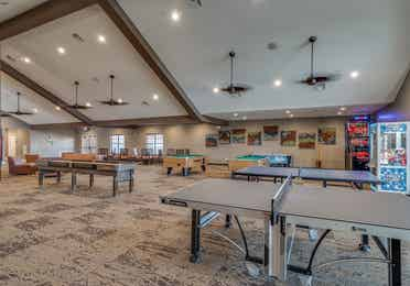 Game room with two ping pong tables, two pool tables, a pop-a-shot machine, claw machine, and seating at Piney Shores Resort in Conroe, Texas