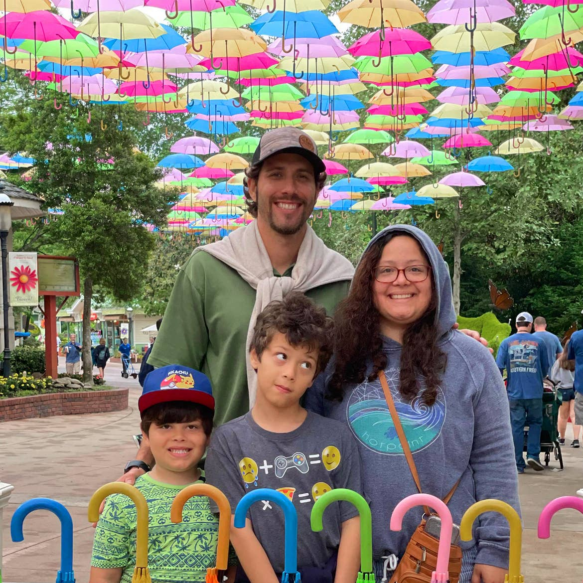 A family of four stand under a colorful umbrella display outdoors.