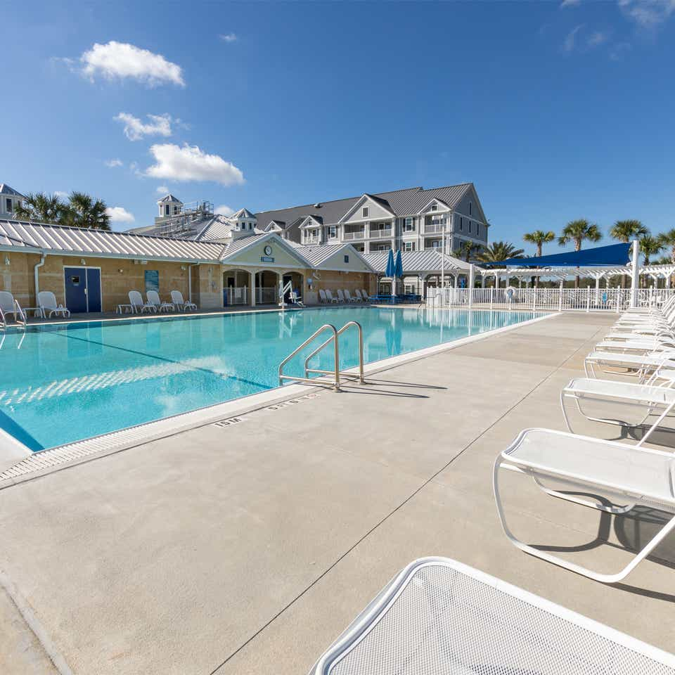 Outdoor pool with lounge chairs at Orlando Breeze Resort near Orlando, Florida.