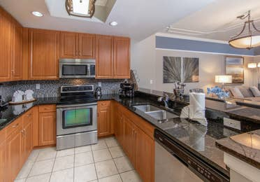 Full kitchen with stainless steel microwave, oven, and sink in a three-bedroom villa at Sunset Cove Resort in Marco Island, Florida