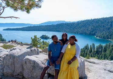 Karen and her family at Emerald Bay State Park with the gorgeous forest, mountains and lake as a backdrop.