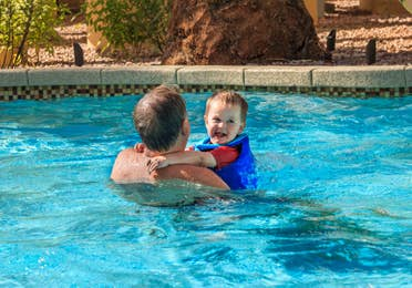 Man holding a young child in a swimming pool