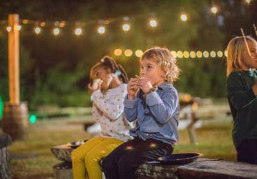 Two toddlers sitting on a bench eating s'mores