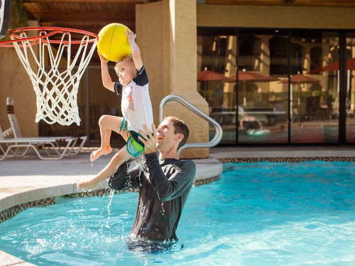Adult and child playing pool basketball at Scottsdale Resort in Scottsdale, Arizona.
