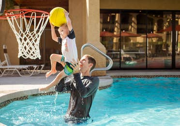 Adult and child playing pool basketball at Scottsdale Resort in Scottsdale, Arizona.