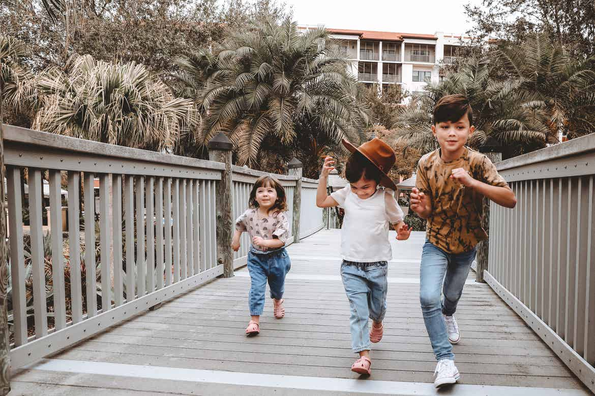 Featured contributor, Mia St. Clair's children, Poppy Bleu (left) Roux (middle) and Grey (right), run across the boardwalk at our Orange Lake Resort in Orlando, FL.