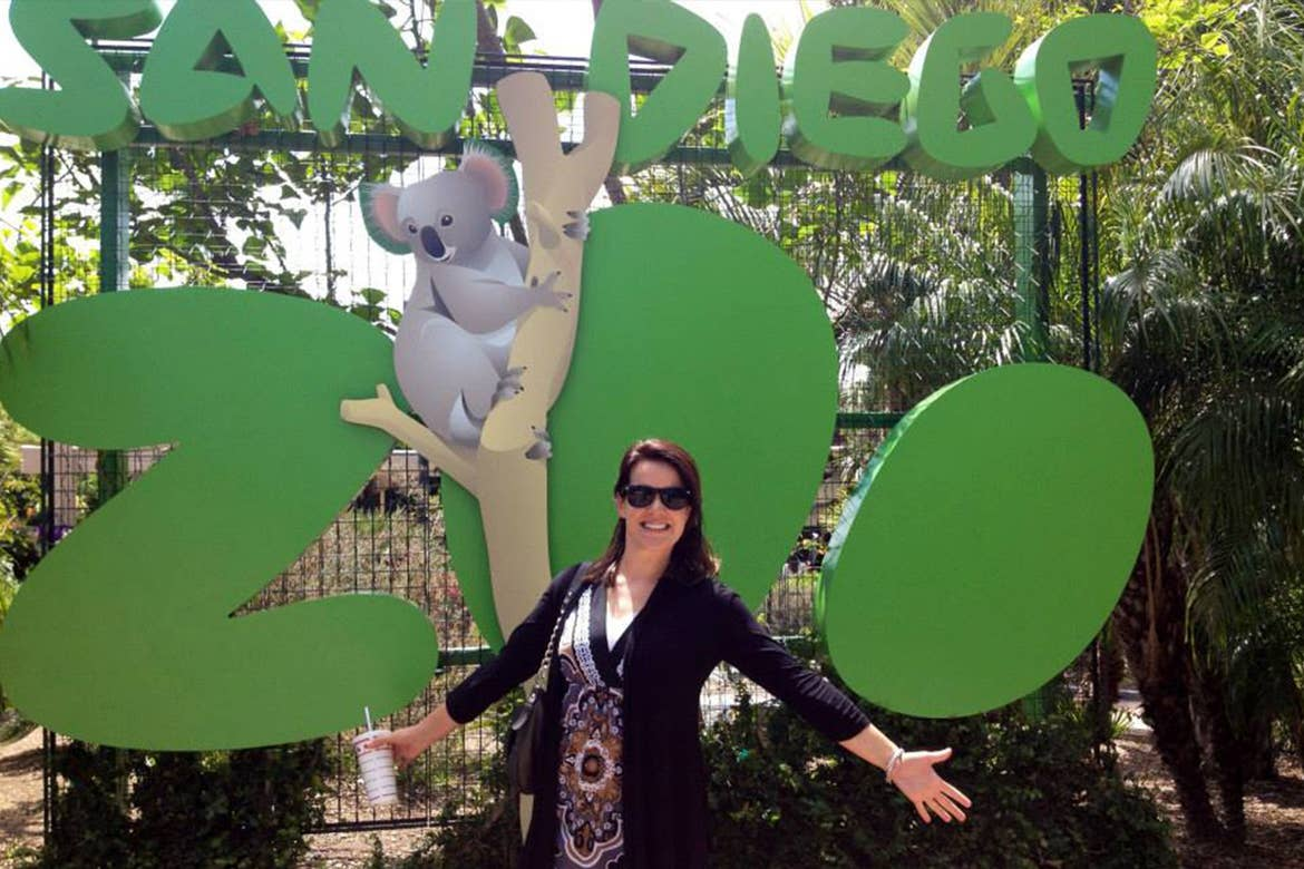 Jenn C. Harmon wears a black cardigan and patterned blouse in front of a green marquee that reads, 'San Diego Zoo'  with a koala graphic.