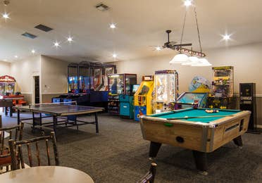Game room with pool table, ping pong table and arcade games at Holiday Hills Resort in Branson, Missouri.