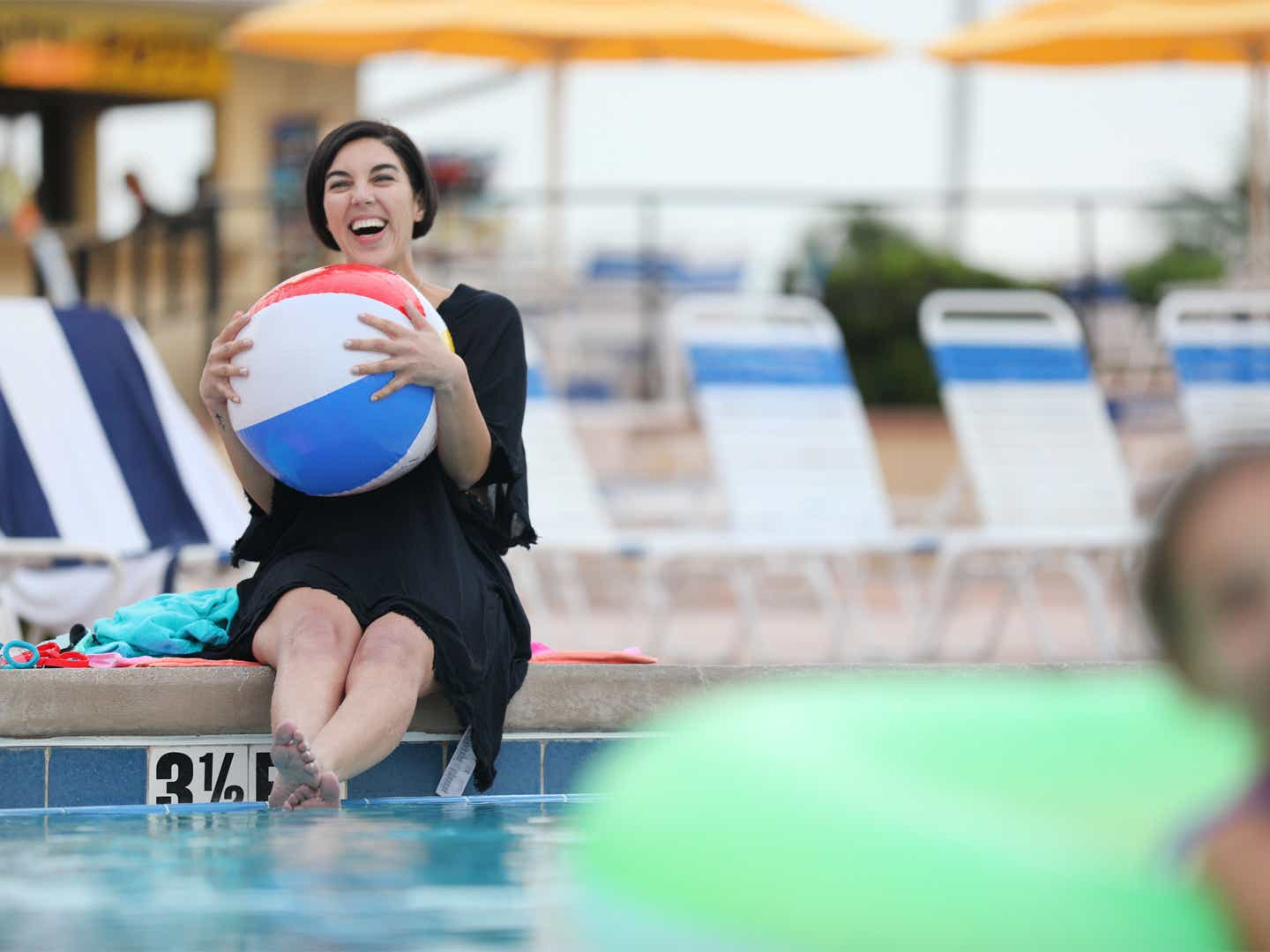 Woman holding beach ball by pool