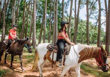 Two guests riding horses in forest at Villages Resort in Flint, Texas.