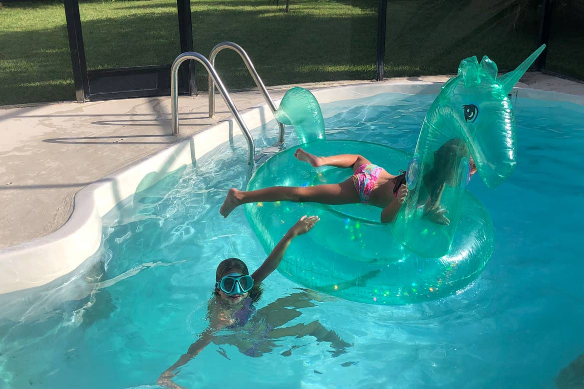 Featured Contributor, Chris Johnston's two daughters, Kyler (left) and Kyndall (right), wear snorkel gear while swimming in the pool around an inflatable unicorn tube.