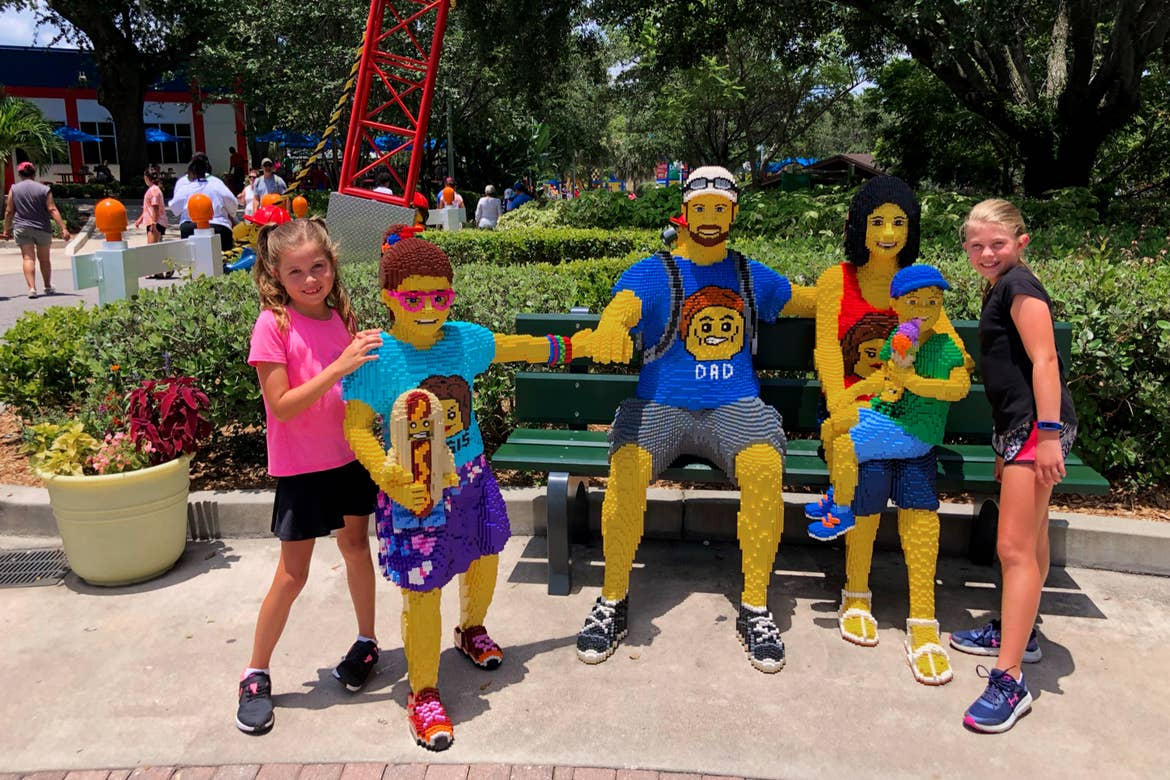 Two young girls (far left and far right) pose with a LEGO family on a bench.