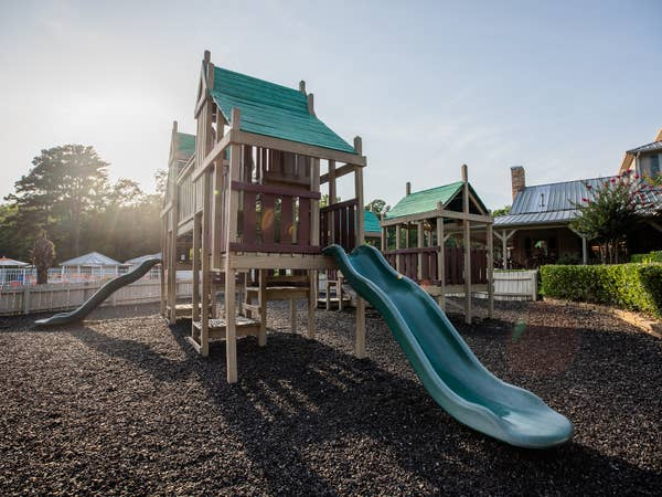 Outdoor playground with hunter green slides at Villages Resort in Flint, Texas