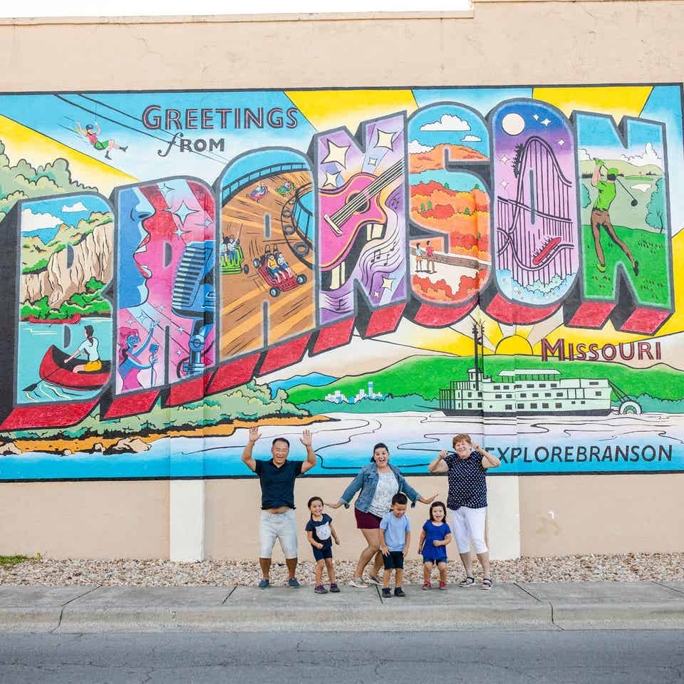 Family in front of Greetings from Branson sign near Holiday Hills Resort.