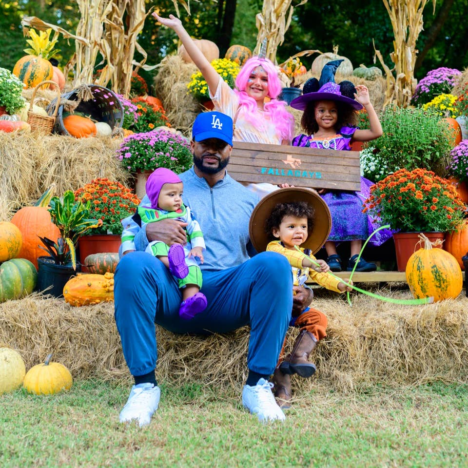 A man, two young toddlers, and two young girls sit on a festive stack of hay bails.
