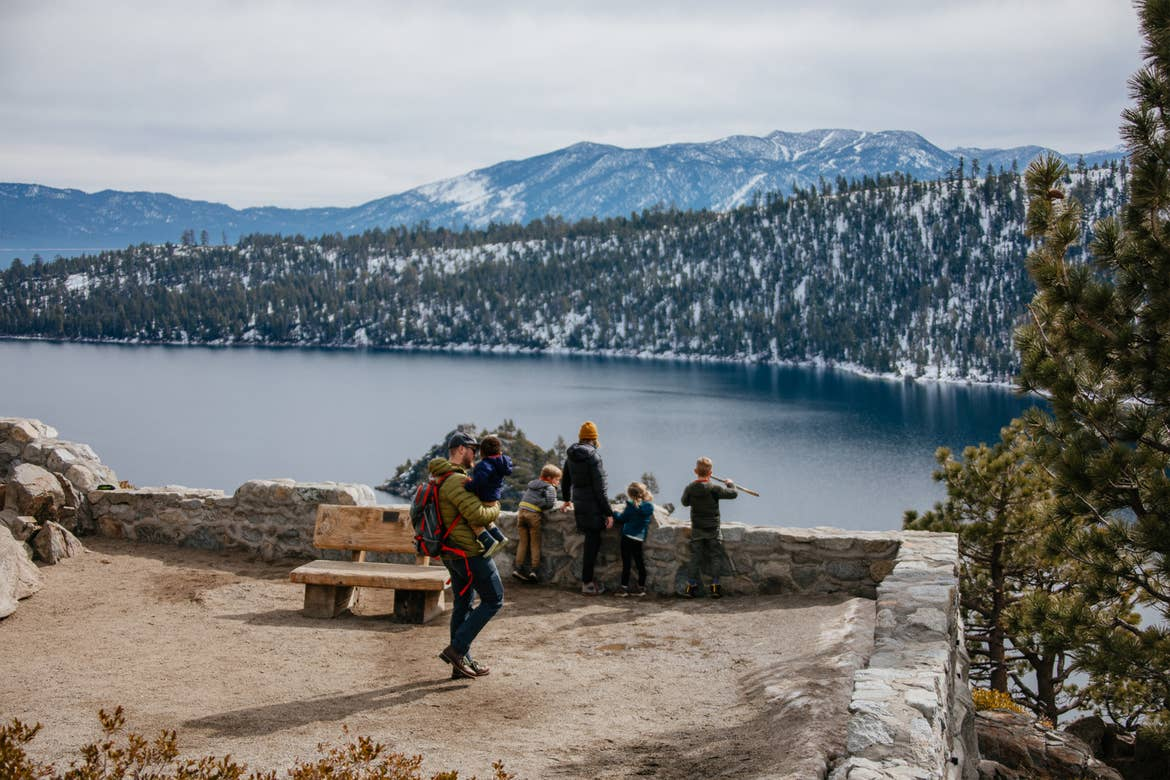 A family stands overlooking Emerald Bay State Park with a gorgeous forest, mountains and lake as a backdrop.
