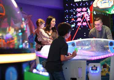 Family playing games in arcade at Orange Lake Resort near Orlando, Florida