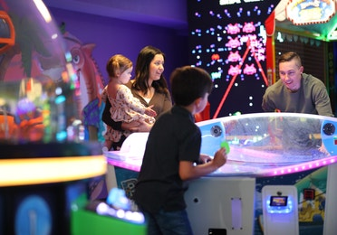 Family playing games in arcade at Orange Lake Resort near Orlando, Florida