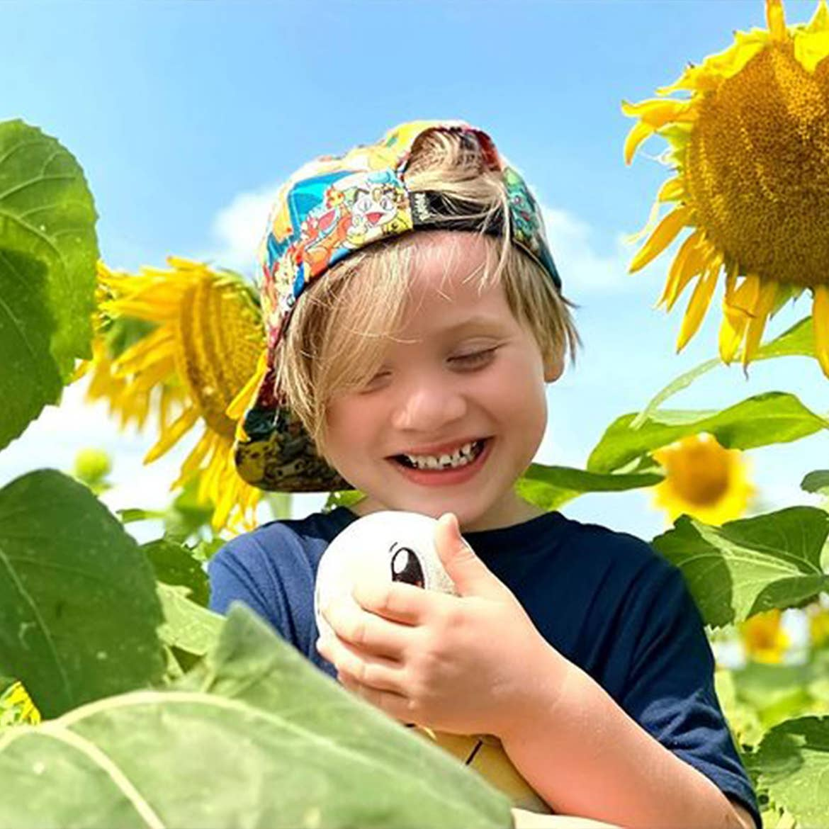 Featured Contributor, Alicia Trautwein's son stands in a sunflower field wearing a hat and holding a plush Squirtle.