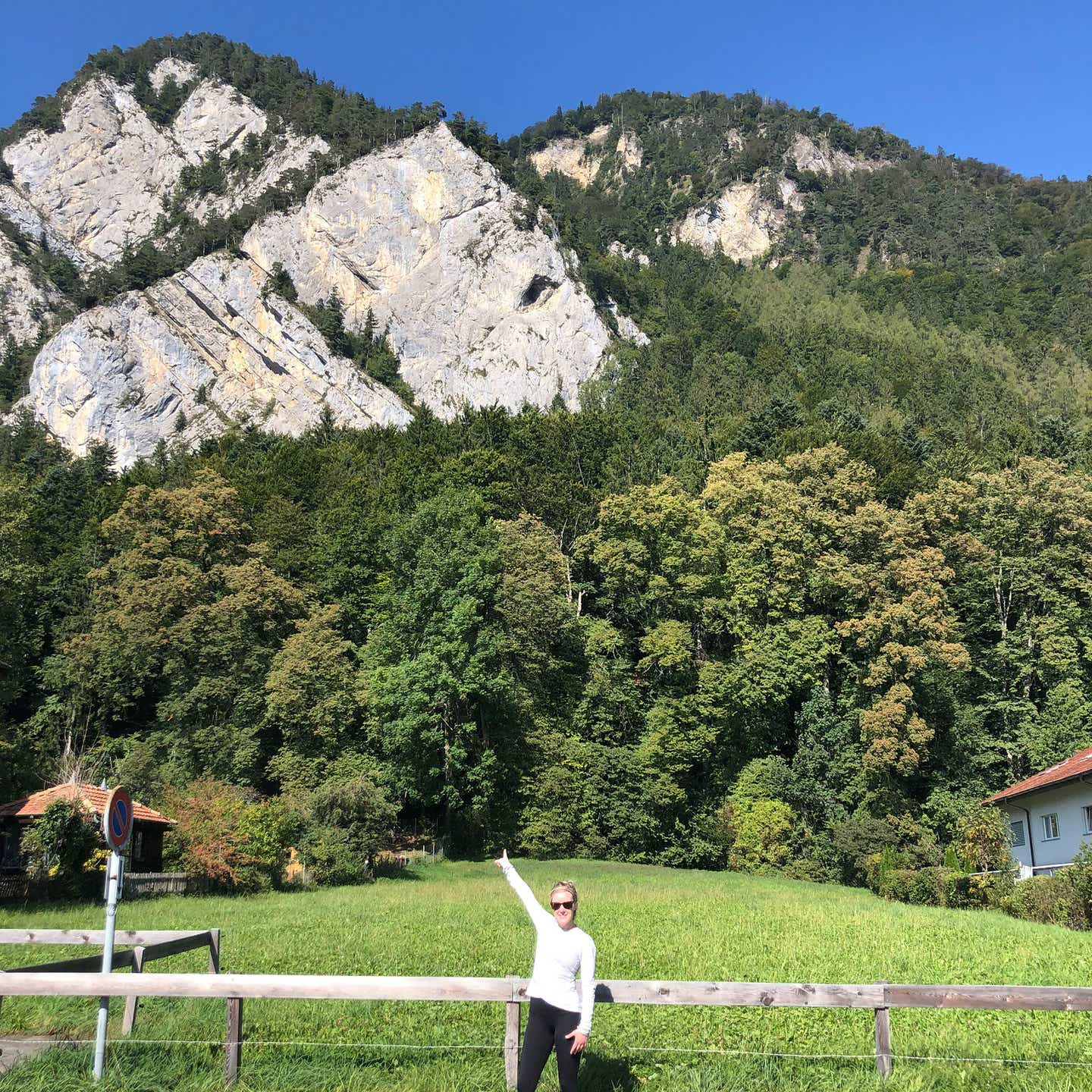 Co-author, Molly, wears a white shirt and black shorts while posing in front of a mountain in Switzerland.