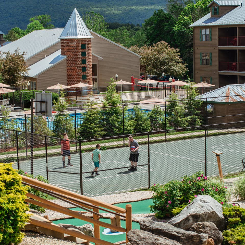 Family playing basketball on sports court at Oak n' Spruce Resort in South Lee, Massachusetts.