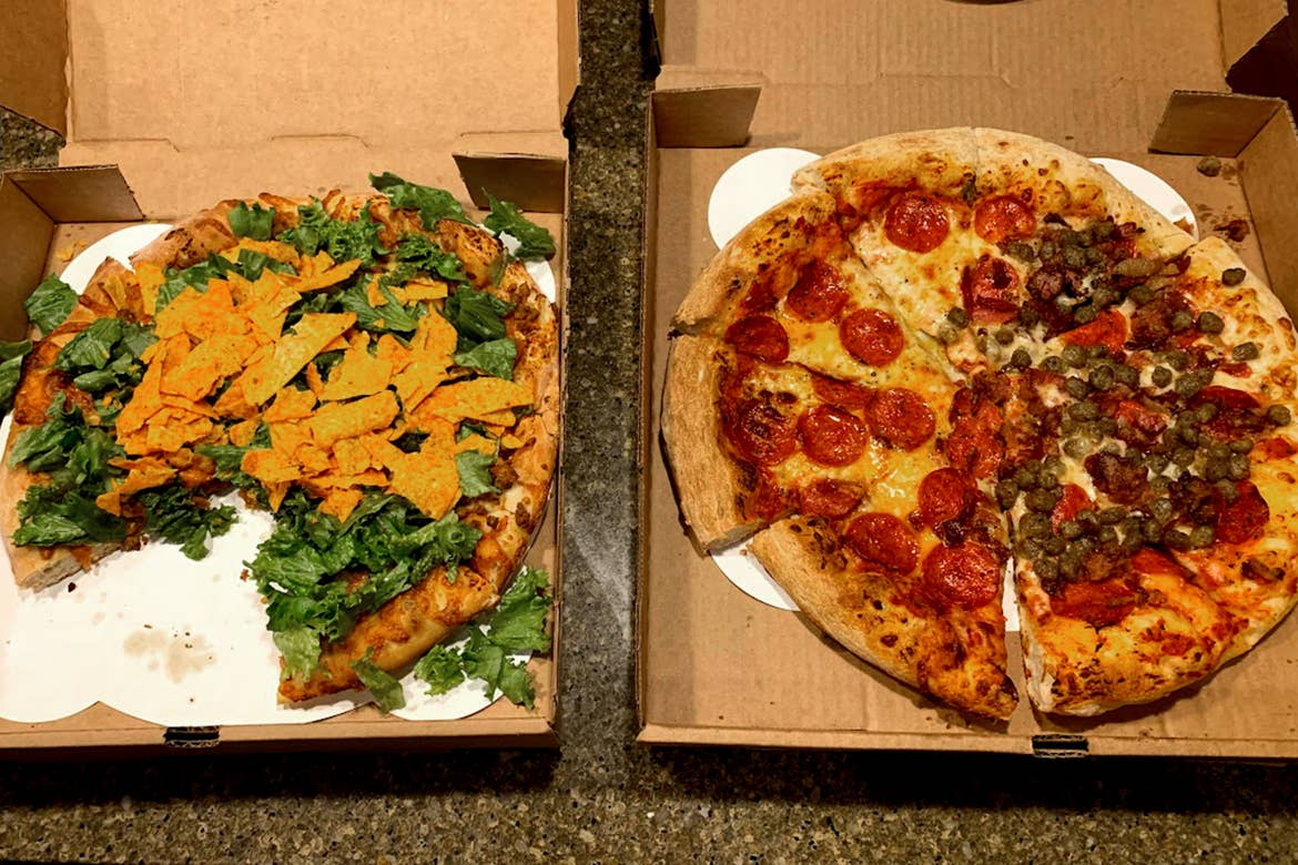 Two pizzas in boxes displayed on a table with various toppings.