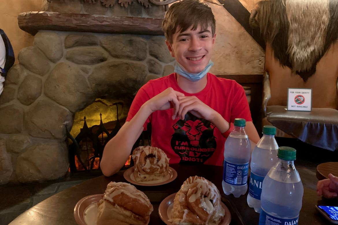 A young man wearing a red t-shirt and a safety mask on his chin sits at a table surrounded by three Dasani water bottles and three cinnamon rolls inside a restaurant.