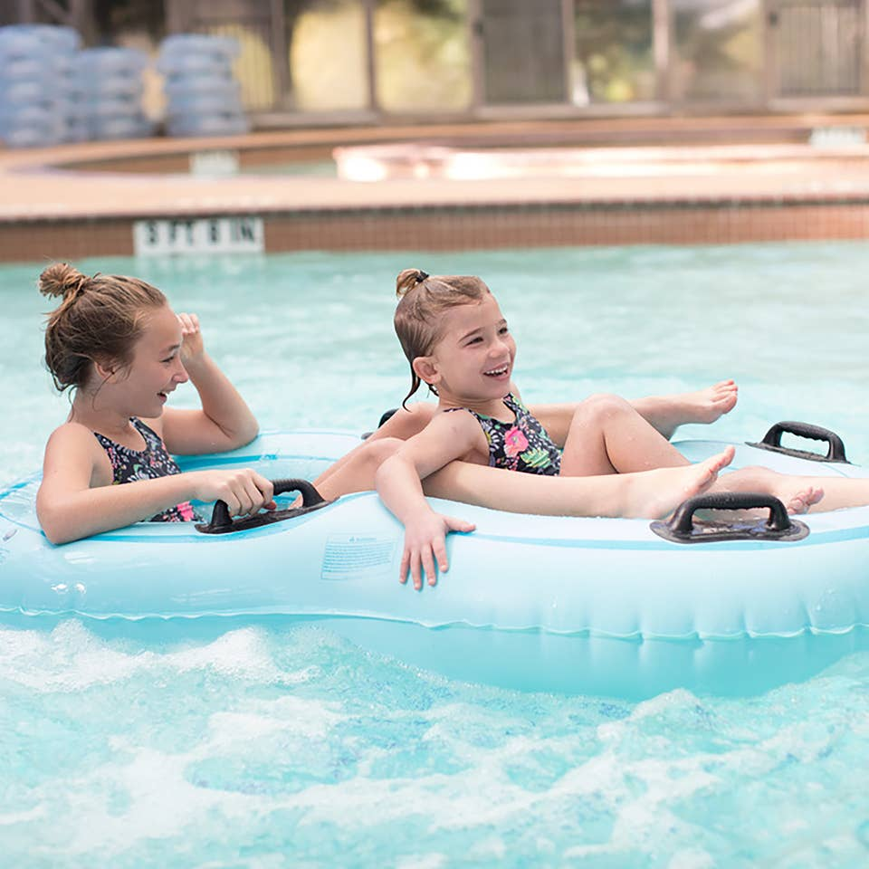Two young girls in an inner tube in a pool at the Villages Resort