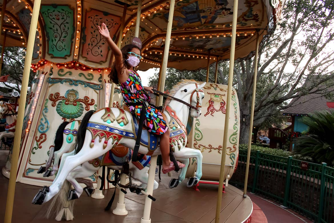 An Asian girl wears a multi-colored dress, blue glasses, and a safety mask while riding a carousel outdoors.
