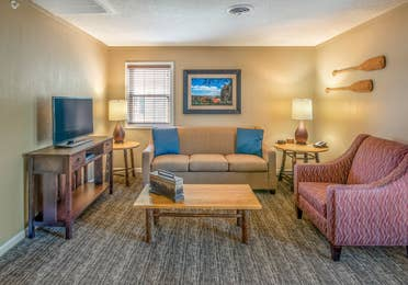 Living room with sofa, chair, and tv at Oak n' Spruce Resort in South Lee, Massachusetts