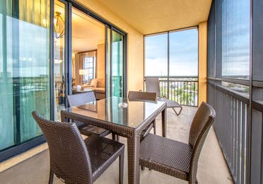 Furnished balcony with sun chair and small table with three chairs in a three-bedroom villa at Sunset Cove Resort in Marco Island, Florida