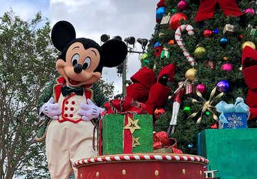 Mickey Mouse stands on the 'Once Upon a Christmastime;' parade float wearing a green jacket with a red lining in front of a large Christmas tree and presents in various green and red wrapping paper.