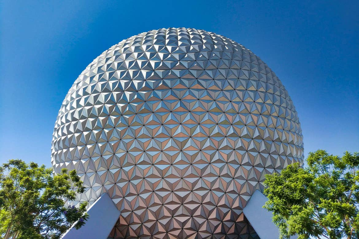The EPCOT geosphere, home of the attraction 'Spaceship Earth' stands under a cloudy-blue sky in EPCOT Theme Park at Walt Disney World Resort.