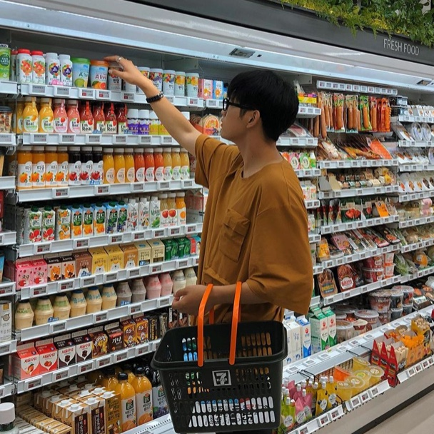 A young man shops in the chilled foods section of a 7-Eleven in Seoul, South Korea.