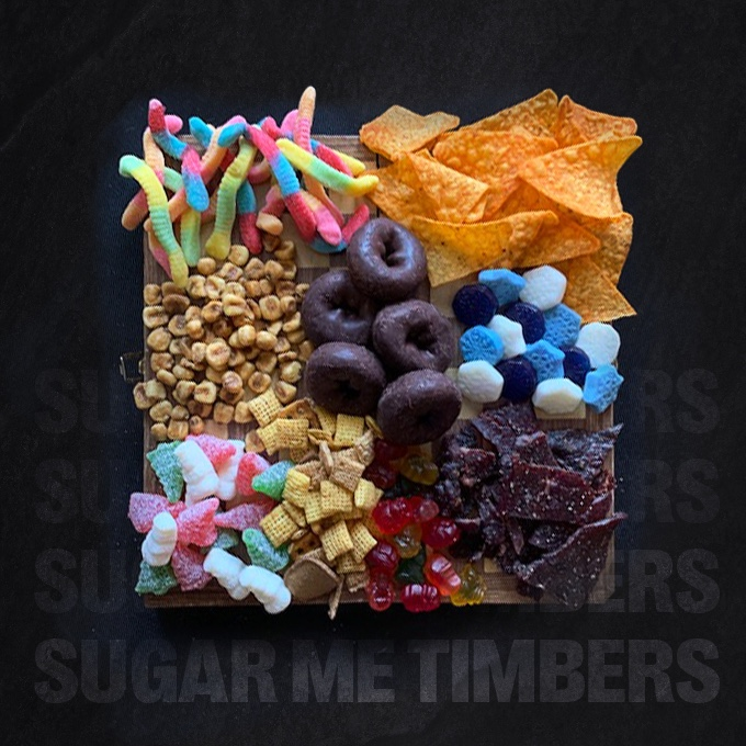 The Sugar Me Timbers charcuterie snack board featuring 7-Select gummis, Jack Link's, mini donuts, Corn Nuts®, Doritos®, and Chex Mix®.
