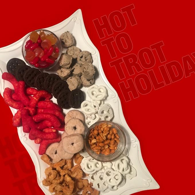 The Hot to Trot Holiday charcuterie snack board featuring Cheetos®, 7-Select™ Peanuts, Cracklin' Curls, Cinnamon Chews, Tropical Gummis, Yogurt Pretzels, Cinnamon Sugar Donuts, Edible Cookie Dough and Sandwich Cookies.