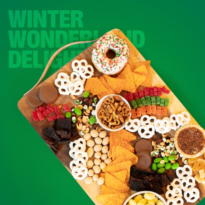 The Winter Wonder and Delight charcuterie snack board featuring 7-Select™ Snack Mix, Edible Cookie Dough, Sour Gummi Bears, Trail Mix, Yogurt Pretzels, Peanut Butter Cups, Mini Pecan Pies, Corn Puffs, Beef Jerky, and Doritos®.