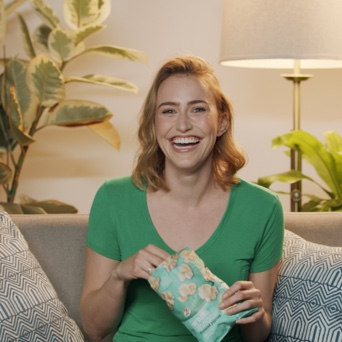 An image of a young blond woman in a green t-shirt sitting in a living room on a couch, laughing and holding a bag of 7-Select white cheddar popcorn.
