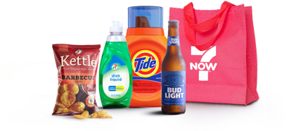 A 7NOW delivery selection featuring the red 7NOW reusable shopping bag, a bottle of bud light beer, Tide liquid laundry detergent, 7-Select liquid dish soap, and 7-Select kettle barbecue chips.