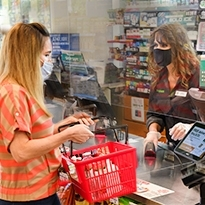 A customer at the cashier to purchase her items is wearing a disposable medical mask, whilst the cashier is wearing a reusable cloth mask.