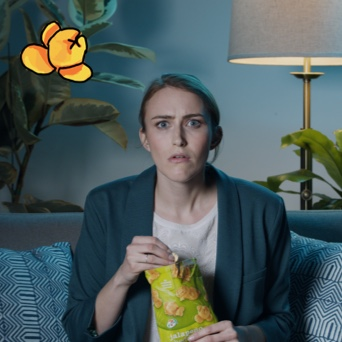 An image of a young blond woman in a dark green blazer and white tshirt sitting in a dark living room on a couch. She is looking intently forward while holding a bag of 7-Select jalapeno cheddar popcorn.