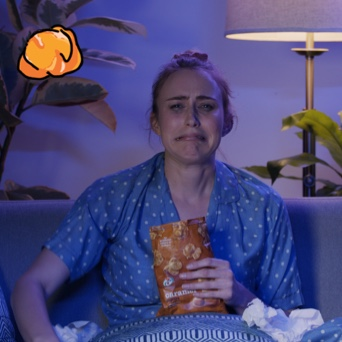An image of a young blond woman in blue & white dot short sleeve pyjamas, sitting in a living room on a couch. She is crying and holding a bag of 7-Select caramel popcorn, and has tissues in her lap.