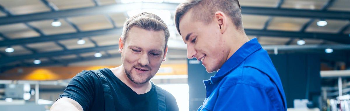 Carreras tecnicas - un mecanico dando instruciones a un estudiante