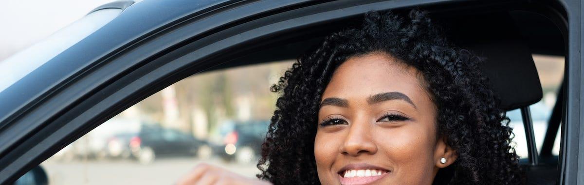 Mujer maneja auto con seguro.