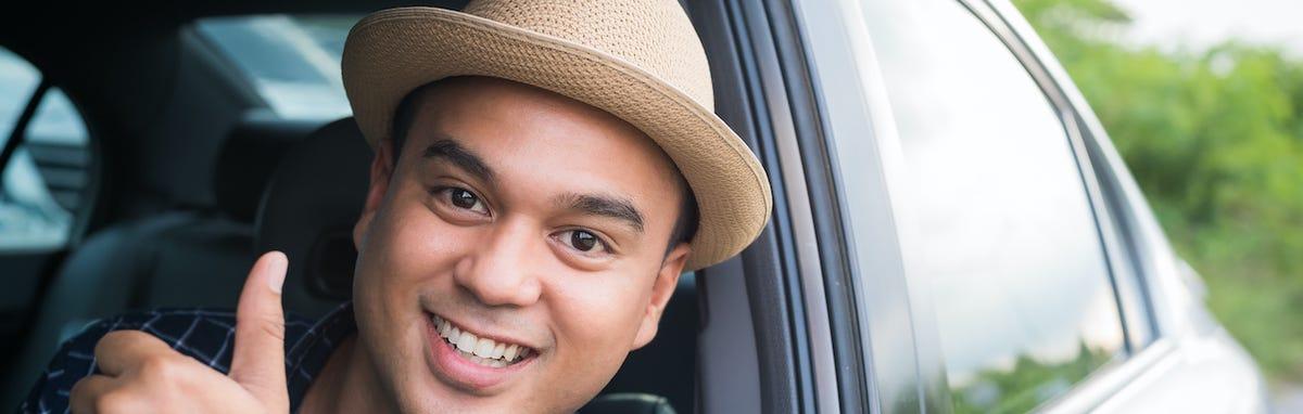 Hombre feliz en su coche porque ahorra más en su seguro de auto
