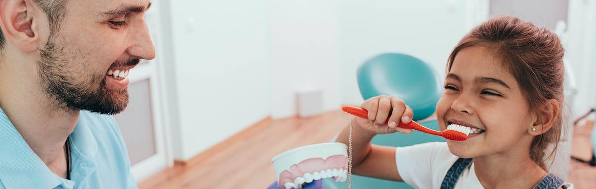 niño aprendiendo los beneficios de la salud bucal al dentista